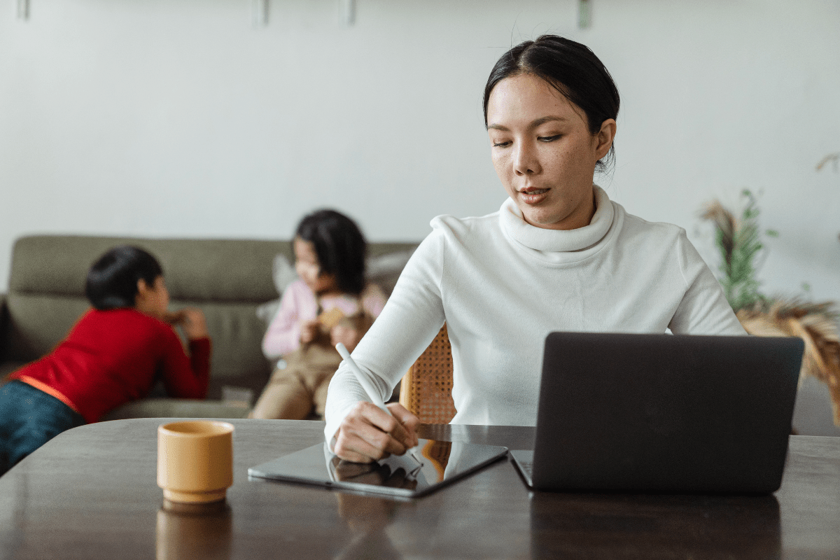 Mom hired and working on laptop with children on couch in background